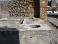 tavern counter at Pompeii with built in holes for food and drink